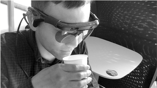 """盲人通过眼镜""""看到""""并顺利拿到了桌上的水杯.图片"""
